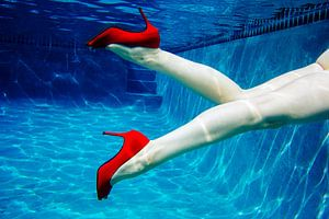 11382168 Vrouwenbenen met rode hoge hakken onder water in zwembad