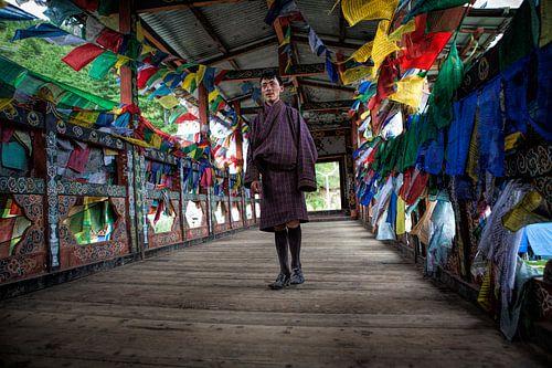 Jonge man in traditionele kleding op loopbrug met gebedsvlaggen in Thimphu Bhutan. Wout Kok One2expo van