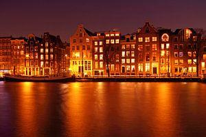 Middeleeuwse huizen langs de Amstel in Amsterdam bij nacht van