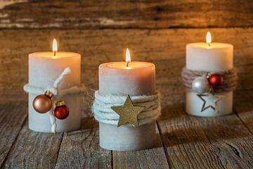 Drie brandende kaarsvlammen met ornamenten en versiering van Alex Winter