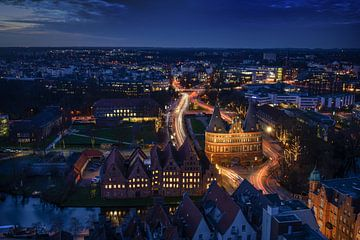 Luftnachtaufnahme der beleuchteten Stadt Lübeck im Winter mit Holstentor und historischen Salzspeich von Maren Winter