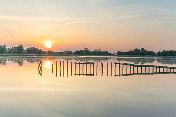 Houten palen in het water bij zonsondergang van Marcel Kerdijk