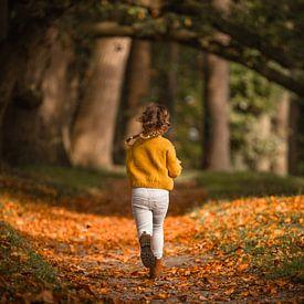 Rennend meisje met vlechtjes op bos pad in de herfst van Mayra Pama-Luiten
