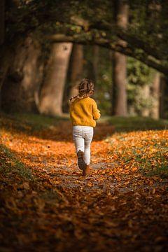 Rennend meisje met vlechtjes op bos pad in de herfst
