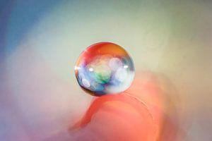 Macro van een waterdruppel met gekleurde lichtinval