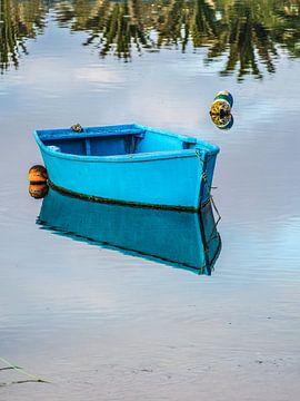 Klein blauw roeibootje spiegelend in stilstaand water van