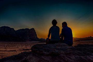 romantisch stel kijkt vanuit een hoge rots , naar de ondergaande zon  in de woestijn  van Wadi-rum   van