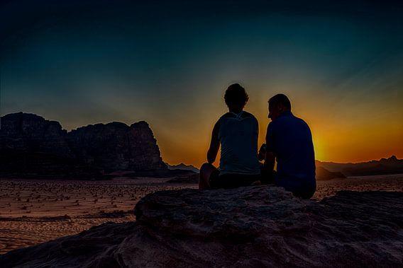 romantisch stel kijkt vanuit een hoge rots , naar de ondergaande zon  in de woestijn  van Wadi-rum