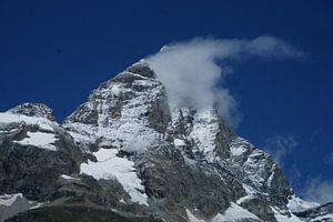 De Matterhorn gaat schuil achter een wolkje met stralend blauwe lucht.