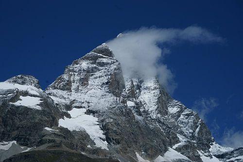 De Matterhorn gaat schuil achter een wolkje met stralend blauwe lucht. van