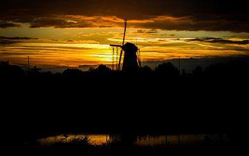 Molen bij zonsondergang en spiegeling in het water von J.A. van den Ende