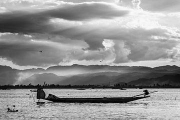 Zwart-wit foto van een visser die zijn netten ophaalt tijdens zonsondergang op het Inle meer in Myan van Twan Bankers