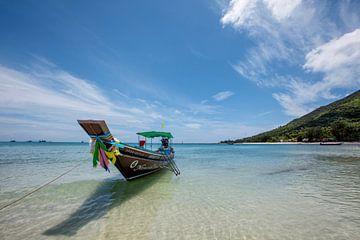 Tropischer Urlaub. Longtailboot an einem tropischen Strand in Thailand. von Tjeerd Kruse