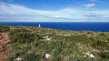 Zicht op de antieke vuurtoren Torre del Gerro aan de kust bij Denia. van Gert Bunt