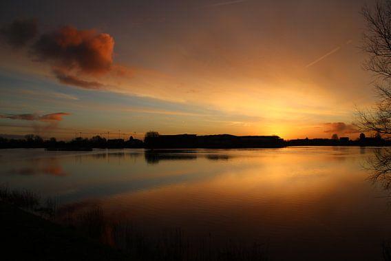 Oranje wolken reflecteren op het water van de Hollandsche IJssel tijdens zonsopkomst