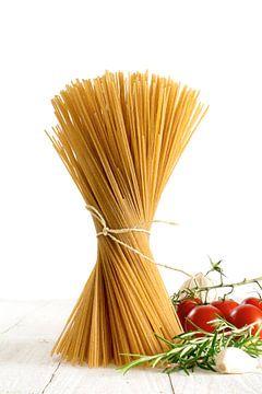 bouquet de spaghettis complets debout sur un bois blanc avec quelques tomates et herbes isolées sur  sur Maren Winter