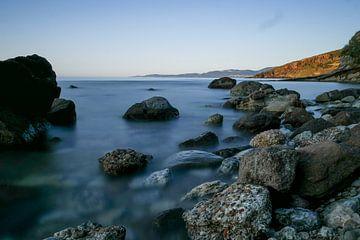 stenen strand met zee en land.