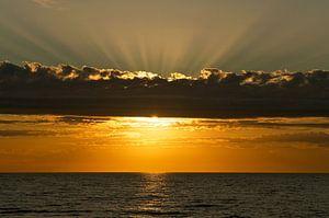De Nederlandse kust: zonsondergang met prachtige wolken en lichtstralen over de Noordzee van