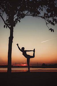 Yogapose als silhouette tijdens de ondergaande zon