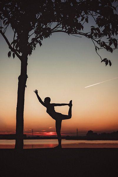 Yogapose als silhouette tijdens de ondergaande zon van Mijke Bressers