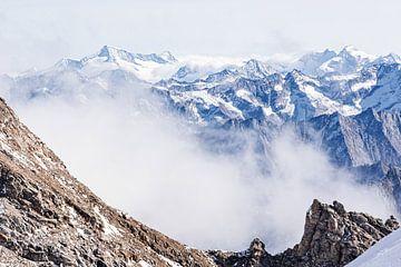 Sfeervolle compositie van hoge bergtoppen in de wolken. Een combinatie van warme en koude kleuren van Hidde Hageman