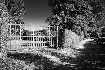Op slot door poort / hek in het zwart wit schaduw landschap van Limburg van Dorus Marchal