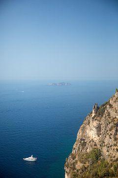 Weißes Boot im Meer vor der Küste eines steilen Berggebiets von Esther Mennen