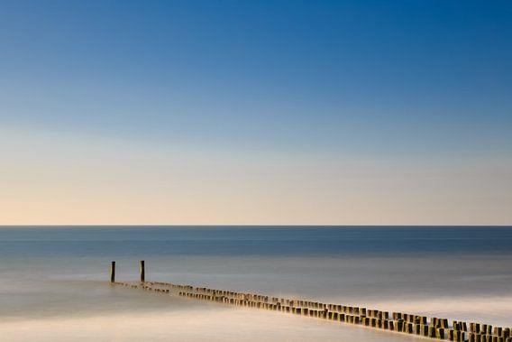 Golfbreker aan het strand in het water. van Robert Wiggers