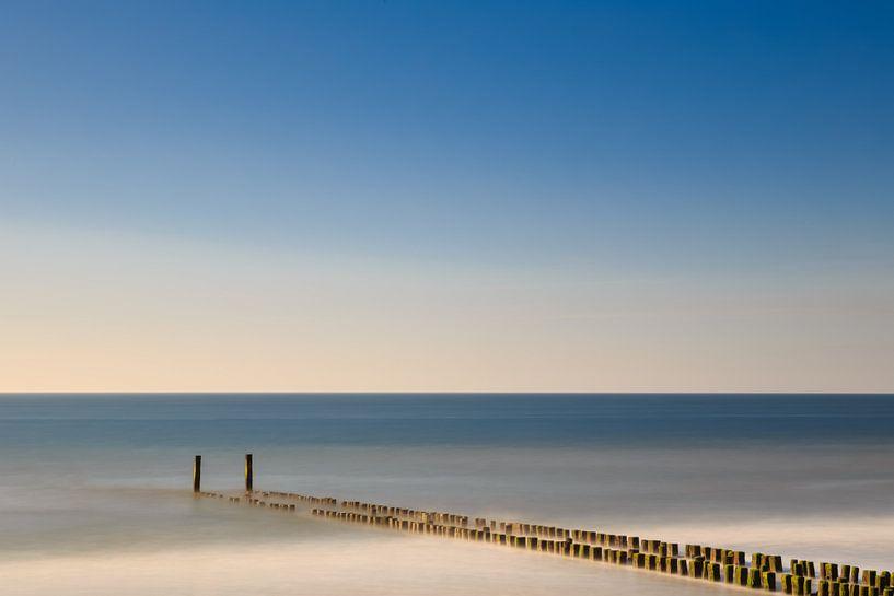 Golfbreker aan het strand in het water. sur Robert Wiggers