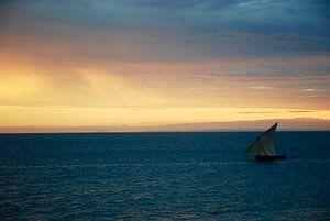 Vissersbootje tegen de zonsondergang in Zanzibar van