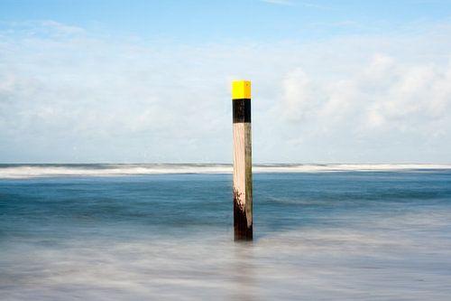 Strandpaal omringd door water van Hans Kwaspen