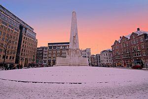 Besneeuwde dam met het nationaal monument in de winter in Amsterdam bij zonsondergang