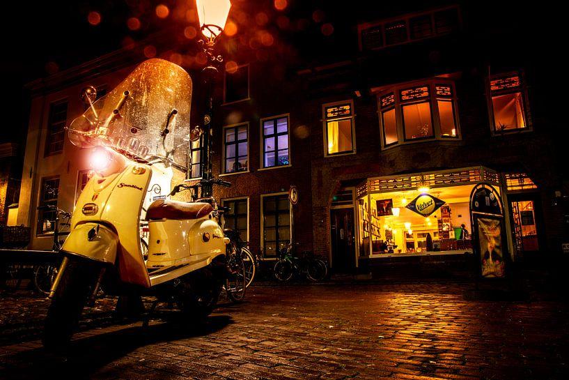 Een regenachtige koopavond, platenzaak Velvet is geopend. Een Vespa maakt het plaatje compleet in ee van Studio de Waay
