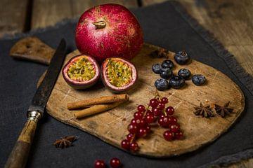 Houten snijplank met granaatappel, passievrucht, bessen, kaneelstokjes en steranijs van Mayra Pama-Luiten