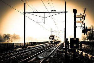 Gekleurde zwart-wit foto van Hollandse trein in mist bij spoorwegovergang van