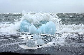 Blauwe ijsschots op vulkaan strand Jokulsarlon met een golf die net op de schots breekt van Jutta Klassen