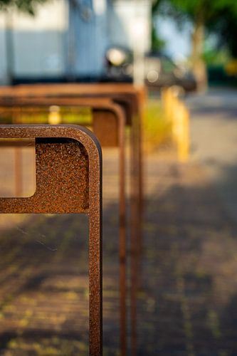 Roestige, bruine fietsenrekken op straat