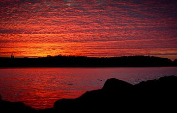 Zonsondergang in Zeeland, de wolkenlucht weerspiegeld in het water van J.A. van den Ende