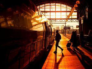 Rezigers lopen over perron naar trein tijdens zonsondergang