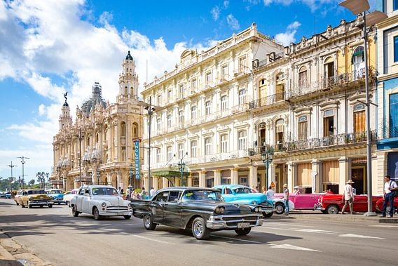 Oldtimer cars drive through the bustling streets of Havana in Cuba