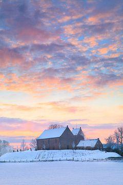 Het bekende wierde kerkje van Ezinge in een wit winter landschap met een mooie zonsopkomst in Gronin van Bas Meelker