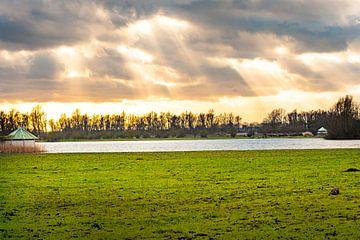 Ondergaande zon door de wolken met mooi licht van Brian Morgan