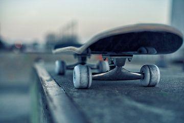 Skateboard op rail in skatepark bij avondschemering van