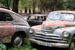 Verlassener Oldtimer auf einem Feld. von Roman Robroek