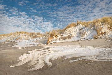 Duinen met poederlaagje sneeuwen prachtige structuren in het zand.