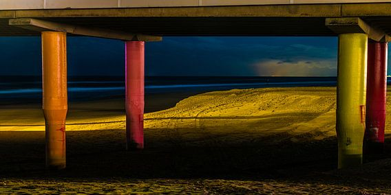 Kleurrijke avond opname van peilers onder de pier van Scheveningen