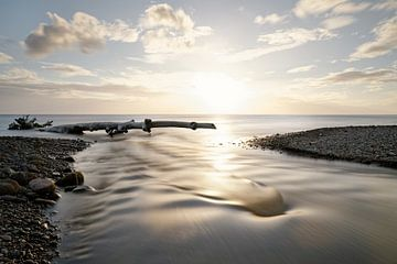 Zonsondergang aan zee met rivier en drijfhout van Ralf Lehmann