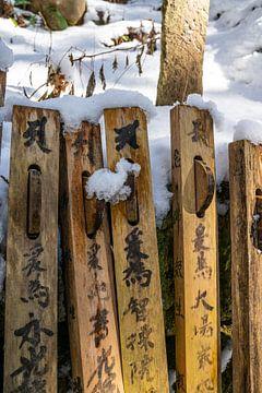 Houten paaltjes met tekst in de sneeuw van Mickéle Godderis