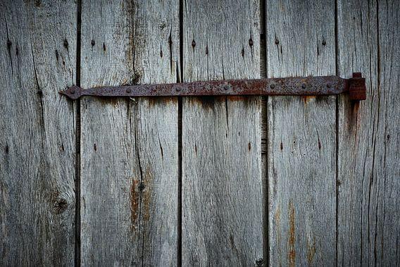 Oud roestig scharnier op een verweerde houten schuur