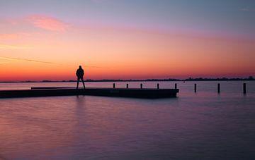Zonsondergang met persoon op steiger, Loswal - Kudelstaart van Photography by Cynthia Frankvoort
